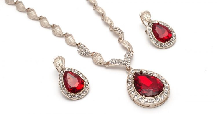 gold necklace and earrings with rubies isolated on white